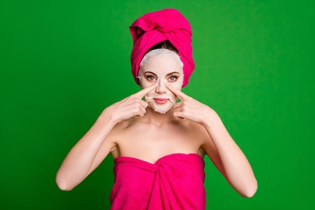 Nahaufnahme einer hübschen dame mit turban auf dem kopf, die eine gesichtsmaske aufträgt, die die nasenfixierung einzeln auf hellgrünem farbhintergrund berührt