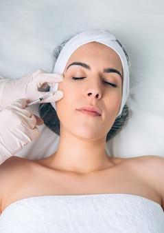 Nahaufnahme einer hübschen frau, die eine kosmetische injektion ins gesicht bekommt, wie ein teil der klinikbehandlung. medizin-, gesundheits- und schönheitskonzept.