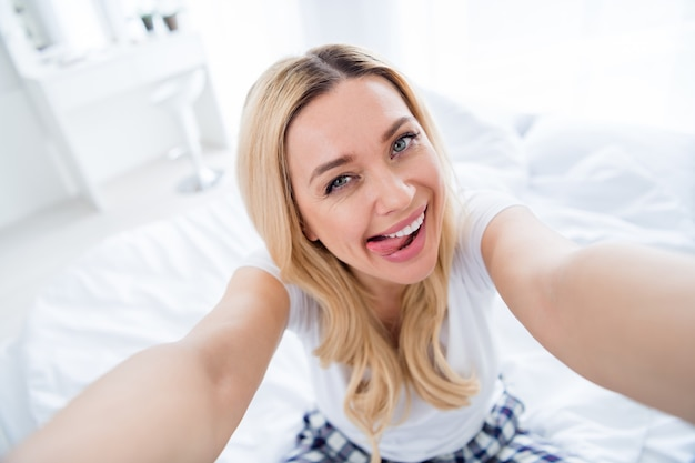 Nahaufnahme einer hübschen lustigen dame, die selfies macht, die zunge aus dem mund stecken?