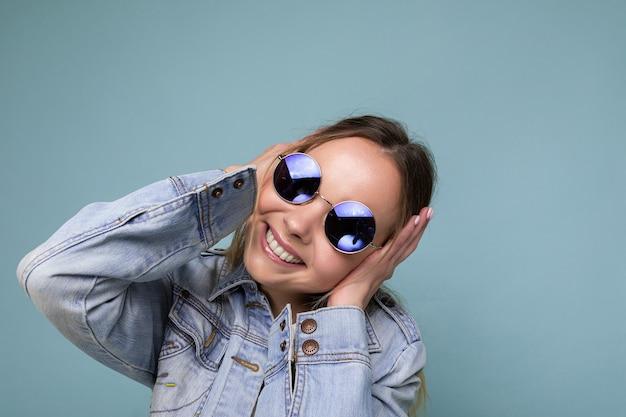 Nahaufnahme einer hübschen, positiv lächelnden jungen blonden frau, die eine blaue jeansjacke und eine stylische sonnenbrille trägt, isoliert über der blauen hintergrundwand, die die kamera anschaut und spaß hat.