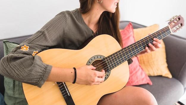 Nahaufnahme einer jugendlichen, die auf dem sofa zu hause spielt gitarre sitzt