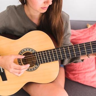 Nahaufnahme einer jugendlichen, die gitarre spielt
