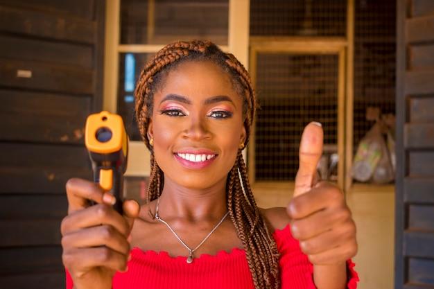 Nahaufnahme einer jungen afrikanischen frau, die ein infrarot-stirnthermometer (thermometerpistole) hält, um die körpertemperatur auf virussymptome zu überprüfen - konzept des epidemischen virusausbruchs und daumen hoch