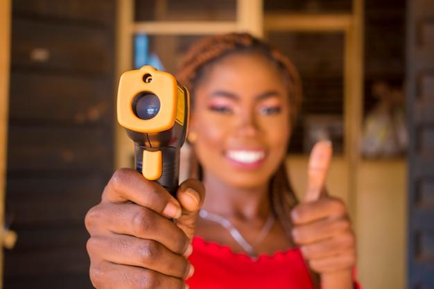 Nahaufnahme einer jungen afrikanischen frau, die ein infrarot-stirnthermometer (thermometerpistole) hält, um die körpertemperatur auf virussymptome zu überprüfen - konzept des epidemischen virusausbruchs und daumen hoch Premium Fotos