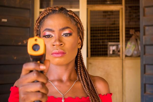 Nahaufnahme einer jungen afrikanischen frau, die ein infrarot-stirnthermometer (thermometerpistole) hält, um die körpertemperatur auf virussymptome zu überprüfen - konzept des epidemischen virusausbruchs