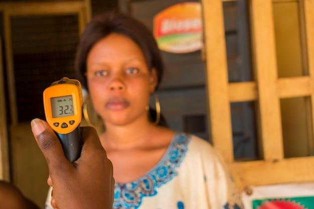 Nahaufnahme einer jungen afrikanischen frau, die ein infrarot-stirnthermometer (thermometerpistole) verwendet, um ihre körpertemperatur auf virussymptome zu überprüfen - konzept des epidemischen virusausbruchs