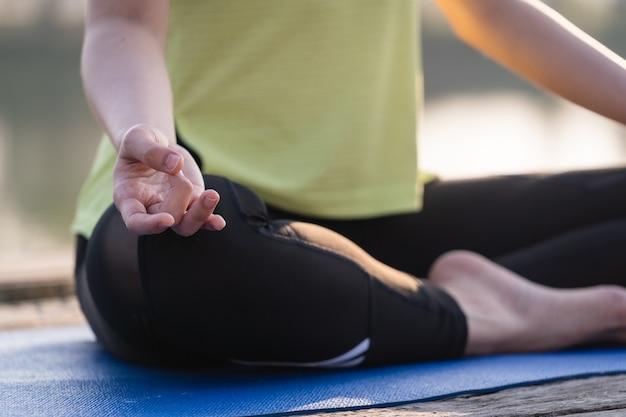 Nahaufnahme einer jungen asiatischen schönen frau, die yoga praktiziert und morgens im lotussitz im freien neben dem see meditiert, um sich zu entspannen und zu beruhigen. harmonie- und meditationskonzept.
