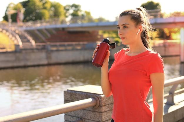 Nahaufnahme einer jungen attraktiven müden sportlerin im freien, trinkwasser aus einer flasche.