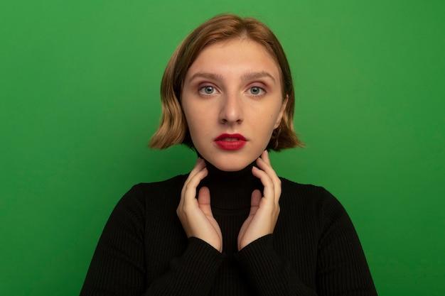 Nahaufnahme einer jungen blonden frau, die auf die vorderseite blickt und den hals isoliert auf der grünen wand berührt