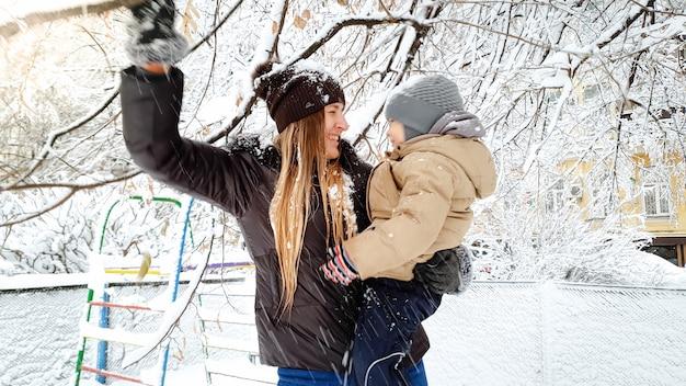 Nahaufnahme einer jungen blonden frau mit ihrem süßen sohn in jacke und hut, die mit schneebedeckten bäumen auf dem spielplatz im park spielt