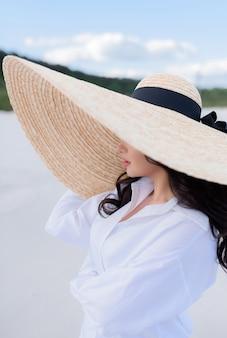 Nahaufnahme einer jungen brünette mit einem großen hut steht auf dem sand