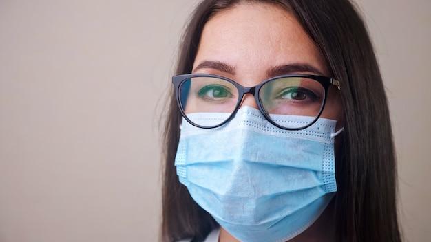 Nahaufnahme einer jungen brünetten ärztin mit brille und hellblauem schutzmaskenexemplar