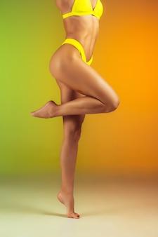 Nahaufnahme einer jungen, fitten und sportlichen frau in stylischer gelber badebekleidung an einer wand mit farbverlauf