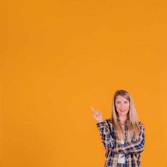 Nahaufnahme einer jungen frau, die aufwärts seinen finger gegen einen orange hintergrund zeigt