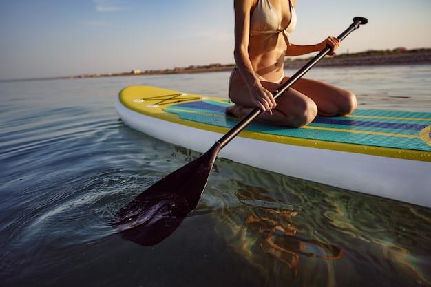 Nahaufnahme einer jungen frau, die bei sonnenuntergang auf einem stand up paddle board sitzt