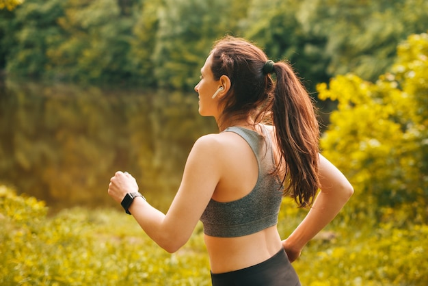 Nahaufnahme einer jungen frau, die bei sonnenuntergang im park im freien läuft?