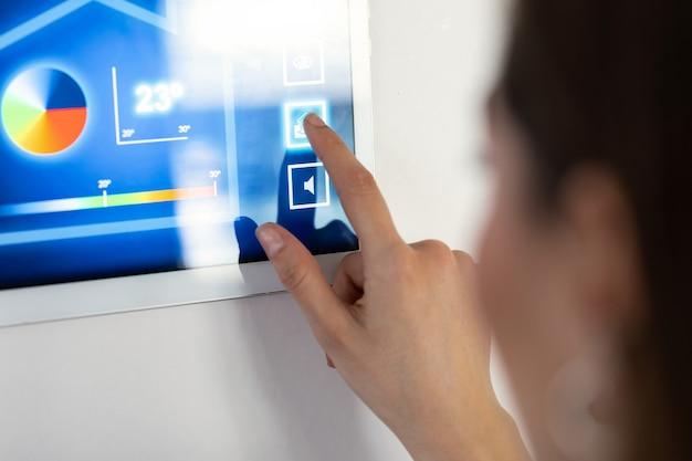 Nahaufnahme einer jungen frau, die das hausautomationssystem auf einem digitalen tablet verwendet, um die temperatur zu regulieren.