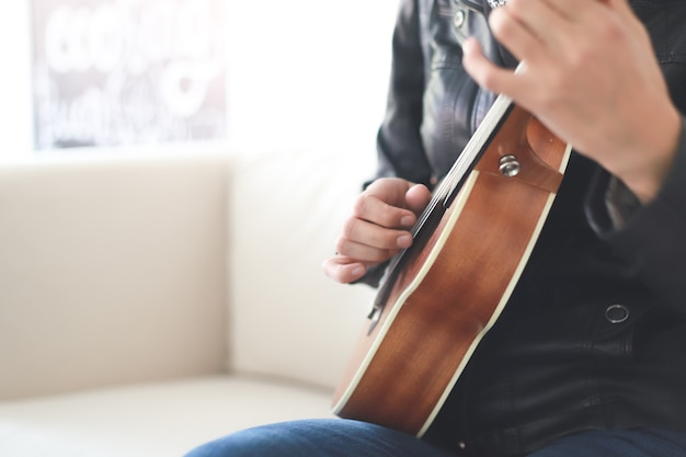 Nahaufnahme einer jungen frau, die die ukulele spielt hipster-frau, die gitarre spielt