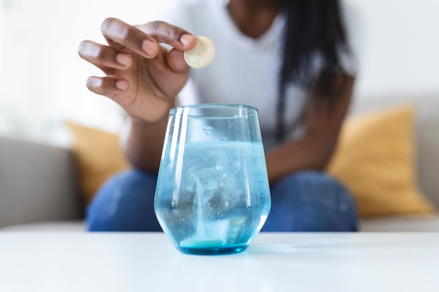 Nahaufnahme einer jungen frau, die ein schäumendes antazidum in ein glas wasser fallen lässt. junge frau legt kaum eine lösliche pille mit einem medikament gegen schmerzen oder einen kater in ein glas wasser