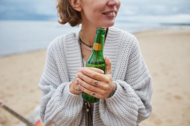 Nahaufnahme einer jungen frau, die eine bierflasche hält, während sie camping am strand im herbst-kopierraum genießt