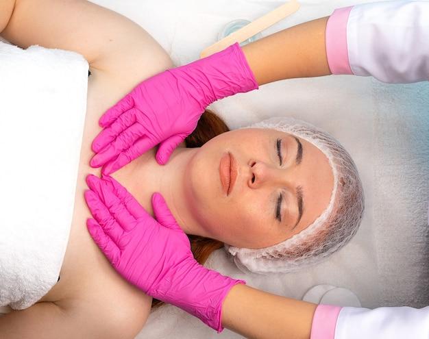 Nahaufnahme einer jungen frau, die eine kosmetische gesichtsmassage in einem schönheitssalon erhält, und die hände des meisters in rosa handschuhen sind sichtbar. gesichtspflege. spa.