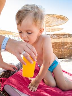 Nahaufnahme einer jungen frau, die ihrem kleinen sohn am meeresstrand ein glas orange gibt