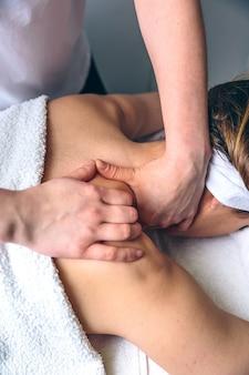 Nahaufnahme einer jungen frau, die in einem klinischen zentrum eine massage auf den schultern erhält. medizin-, gesundheits- und schönheitskonzept.