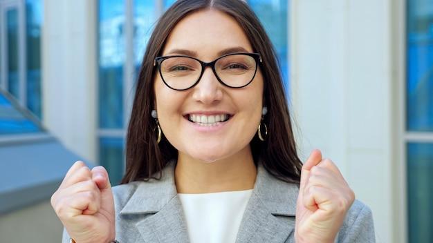 Nahaufnahme einer jungen frau mit brille, die überrascht in die kamera lächelt.