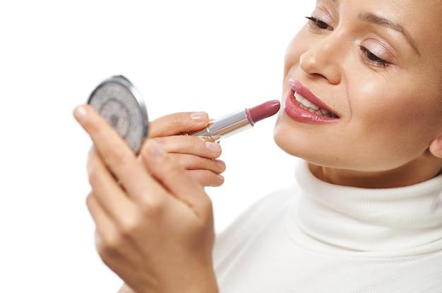 Nahaufnahme einer jungen frau mit dem schönen lächeln, das einen lippenstift auf ihren lippen anwendet und sich auf einen kleinen kosmetischen spiegel betrachtet
