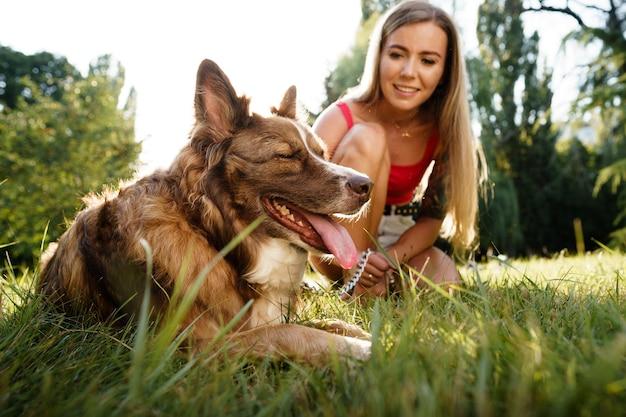 Nahaufnahme einer jungen frau mit ihrem hund, der auf gras im park sitzt?