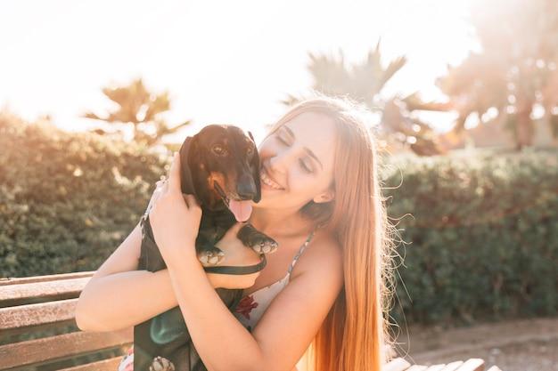 Nahaufnahme einer jungen frau mit ihrem hund, der heraus zunge haftet