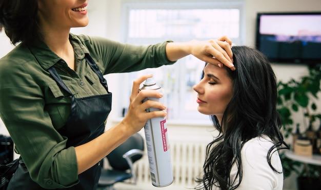 Nahaufnahme einer jungen friseurin, die das haar ihrer kundin mit haarspray besprüht.