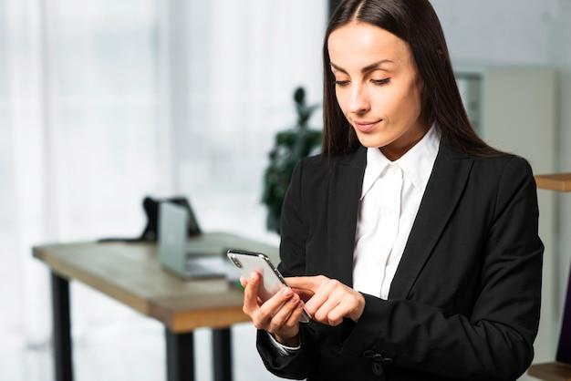 Nahaufnahme einer jungen geschäftsfrau, die im rührenden smartphone des büros steht