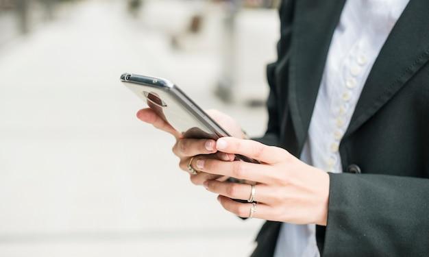 Nahaufnahme einer jungen geschäftsfrau, die smartphone verwendet