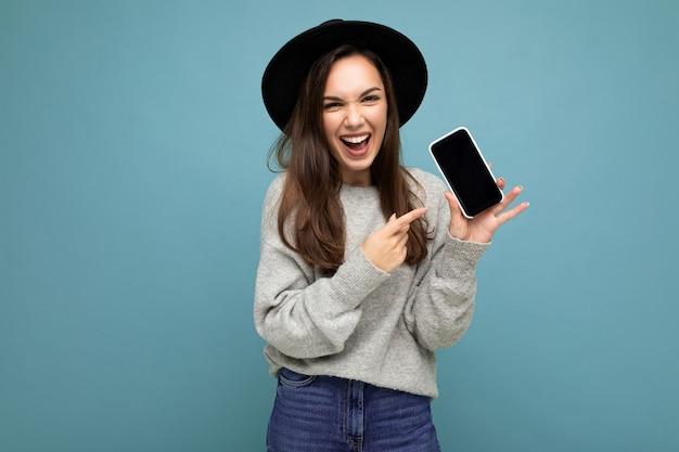 Nahaufnahme einer jungen glücklichen frau mit schwarzem hut und grauem pullover, die das telefon hält und die kamera ansieht, die mit dem finger auf den bildschirm zeigt, der auf dem hintergrund isoliert ist