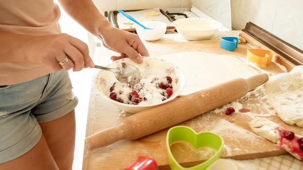Nahaufnahme einer jungen hausfrau, die zucker in eine große schüssel mit fgresh-beeren gießt, während sie soße für kuchen macht