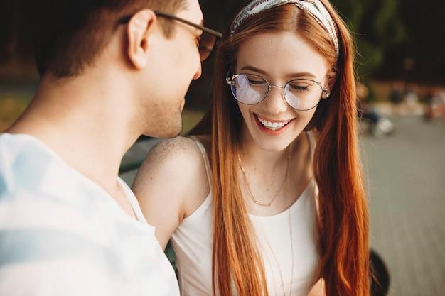Nahaufnahme einer jungen rothaarigen frau mit sommersprossen, die mit geschlossenen augen lachen, die mit ihrem mann datieren. schönes paar, das im freien datiert und spaß hat.