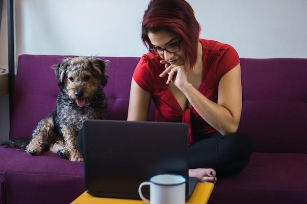 Nahaufnahme einer jungen schönen frau, die mit einem hund vor dem laptop auf dem sofa sitzt