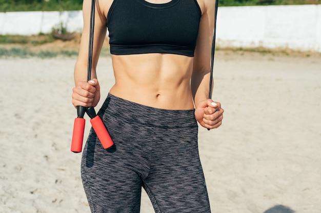 Nahaufnahme einer jungen sportlichen frau in der sportkleidung, die ein rotes springseil auf dem strand hält