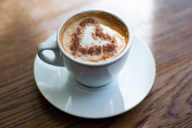 Nahaufnahme einer kaffeetasse auf einem holztisch