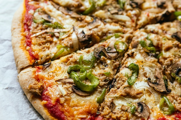 Nahaufnahme einer köstlichen hausgemachten italienischen pizza mit käse, tomaten, pilzen und grünem pfeffer