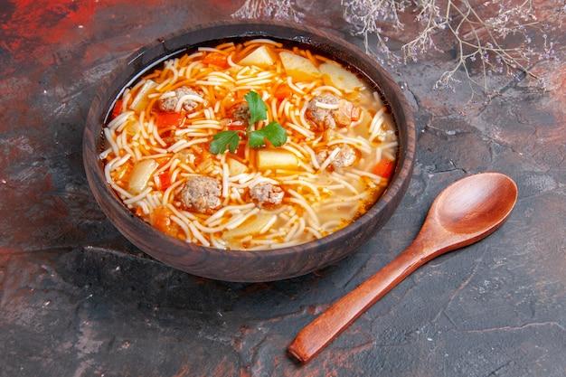 Nahaufnahme einer köstlichen nudelsuppe mit hühnchen in einer braunen schüssel und einem löffel auf dunklem hintergrund