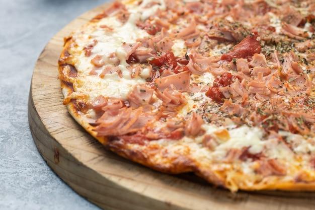 Nahaufnahme einer köstlichen pizza mit geschnittenen würstchen und geschmolzenem käse auf einem brett unter den lichtern