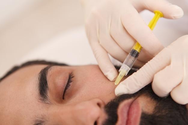 Nahaufnahme einer kosmetikerin, die füllstoff in die falten eines männlichen kunden injiziert