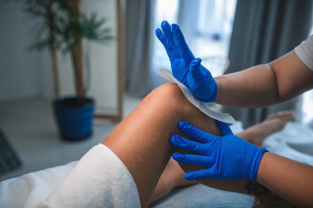Nahaufnahme einer kosmetikerin, die im beauty-spa das bein der frau wäscht?