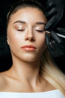 Nahaufnahme einer kosmetikerin in schwarzen handschuhen, die einer jungen frau in einem schönheitssalon permanentes augenlid-make-up auftragen. nahaufnahme