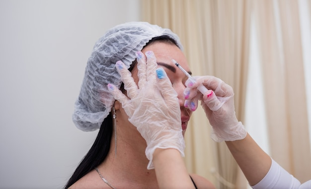 Nahaufnahme einer kosmetikerin in weißer uniform und einer mütze, die schönheitsinjektionen für einen kunden macht