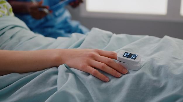 Nahaufnahme einer kranken frau, die auf der krankenstation im bett ruht?