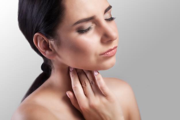 Nahaufnahme einer kranken frau mit den halsschmerzen, die schlecht sich fühlen