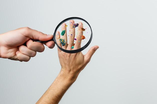 Nahaufnahme einer kranken hand durch lupe, die viren durch hautkontakt 3d-rendering überträgt
